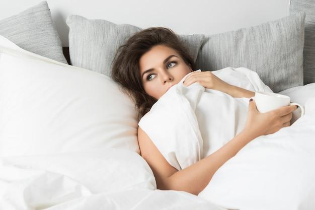 Mujer enferma sentada debajo de una manta