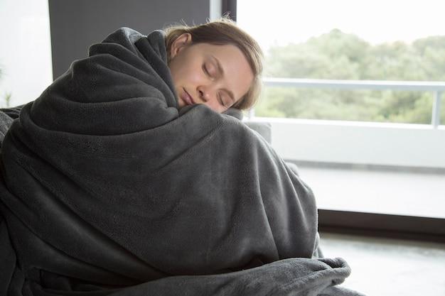 Mujer enferma sentada en el sofá con los ojos cerrados, abrazando las rodillas