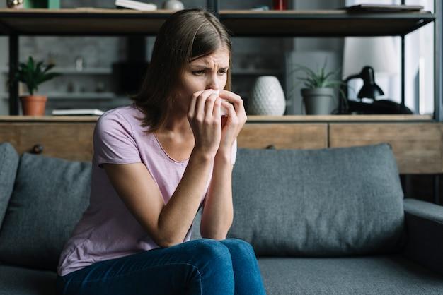 Mujer enferma sentada en el sofá soplando la nariz con un pañuelo de papel