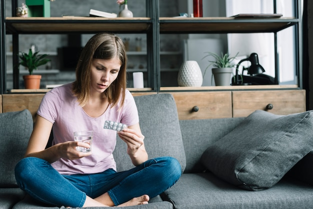 Mujer enferma sentada en el sofá con vaso de agua y pastillas