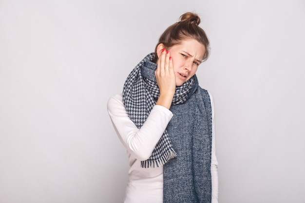 Mujer enferma sosteniendo la mano su cheeh, tiene dolor de muelas. foto de estudio, pared gris