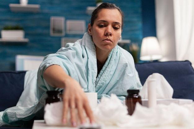 Mujer enferma tomando medicamentos para el virus estacional envuelto en una manta con píldoras caucásicas jóvenes perso ...