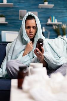 Mujer enferma tomando pastillas de tratamiento médico medicamentos antibióticos para la enfermedad sosteniendo el tarro de pharmaceutica ...