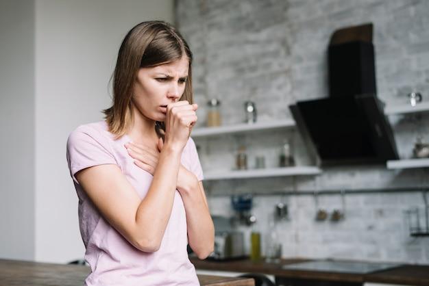 Mujer enferma tosiendo en casa
