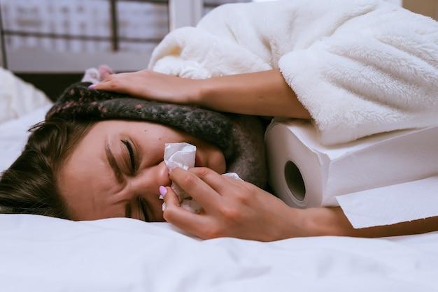 Una mujer enferma yace en una cama y toallas de papel.