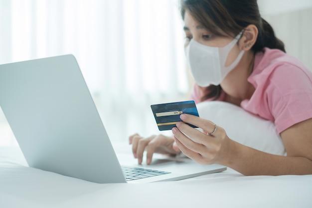 Mujer de enfermedad con mascarilla con tarjeta de crédito y usando la computadora portátil para compras en línea en la cama por la mañana en casa.