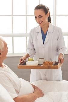 Mujer enfermera en bata blanca médica está sosteniendo una bandeja