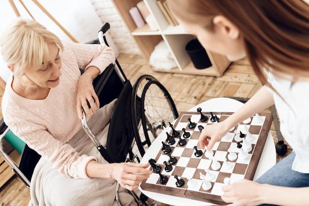 Mujer con enfermera jugar al ajedrez en casa.