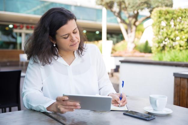 Mujer enfocada haciendo notas, trabajando y usando tableta en café
