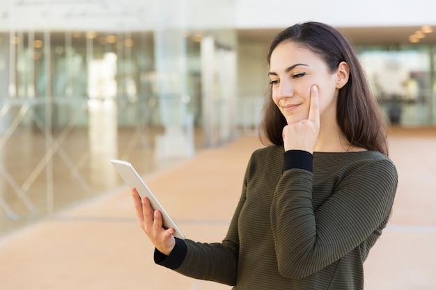 Mujer enfocada pensativa viendo contenido en tableta