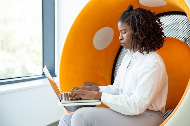 Mujer enfocada con rastas escribiendo en la computadora portátil