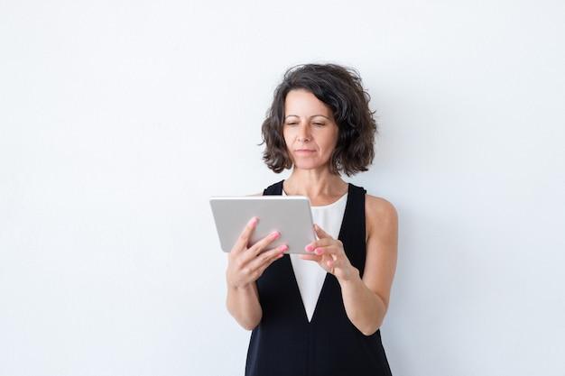 Mujer enfocada seria en casual usando tableta