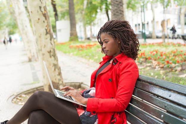 Mujer enfocada usando la computadora portátil en el parque