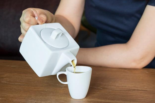 Mujer enjuague una taza de té después de la comida