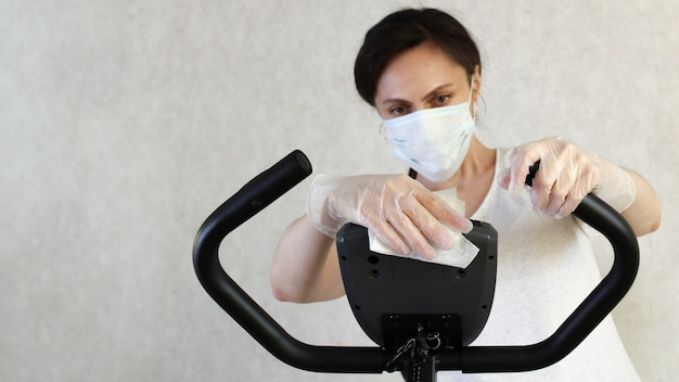 Una mujer enmascarada limpia el simulador con una toallita desinfectante para evitar la propagación del virus. detener el coronavirus. covid-19. lugar para el texto copia espacio