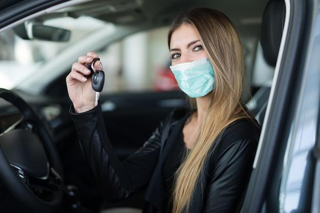 Mujer enmascarada mostrando la llave de su auto nuevo en un salón de venta de autos