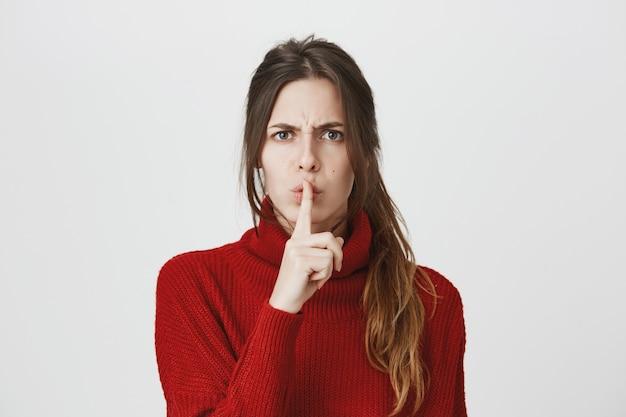 Mujer enojada callar con el dedo presionado a los labios