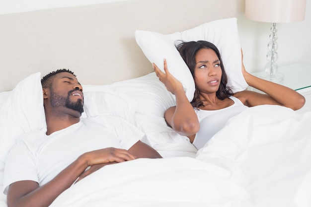 Mujer enojada cubriendo sus orejas con almohadas para bloquear el ronquido