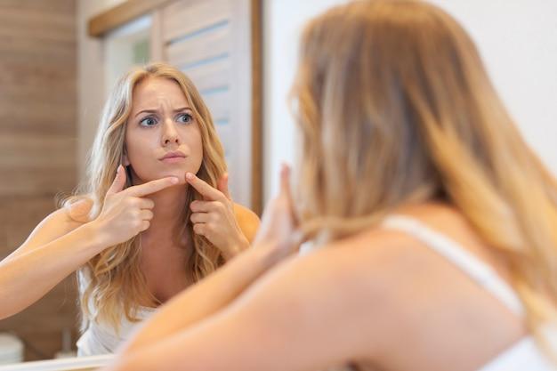 Mujer enojada exprimiendo el grano de la cara