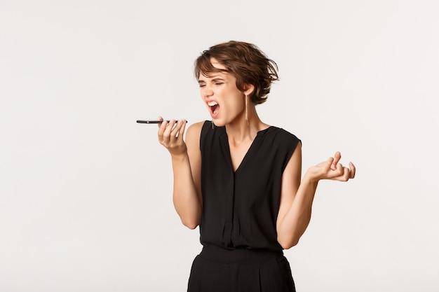 Mujer enojada gritando, grabando un mensaje de voz, gritándole a alguien por teléfono, de pie blanco.