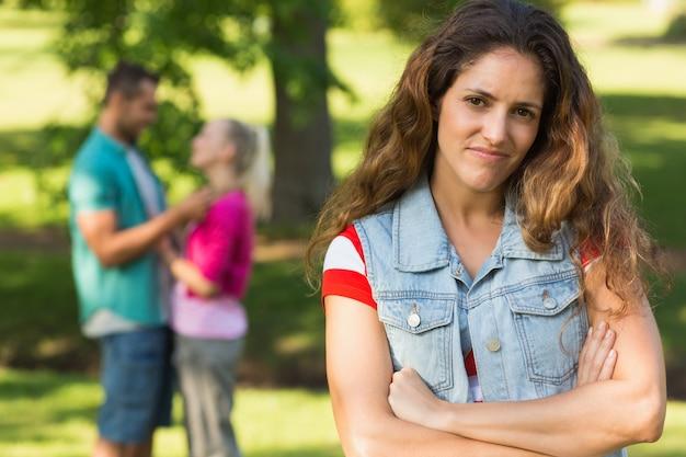 Mujer enojada con hombre y novia en el fondo en el parque
