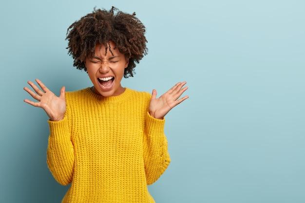 Mujer enojada insatisfecha con un afro posando en un suéter rosa