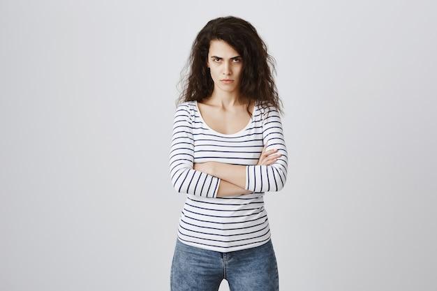 Mujer enojada y molesta cruzan el pecho de brazos y mirando con acusación