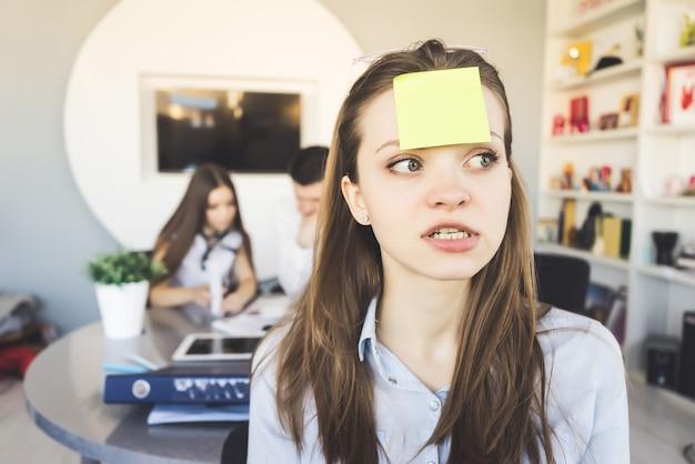 Mujer enojada en oficina con pegatina en la cabeza, estudiante frustrado.