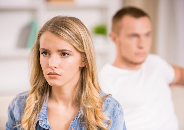 Mujer enojada que se sienta de nuevo a su marido.