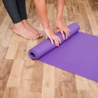 Mujer enrollando alfombra de yoga
