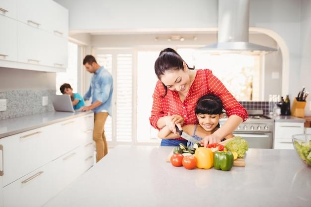 Mujer enseñando a hija a cortar verduras en la mesa