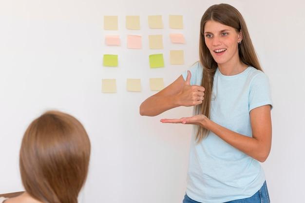 Mujer enseñando lenguaje de señas a alguien