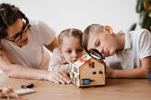 Mujer enseñando a los niños funcionalidades de dispositivos eléctricos