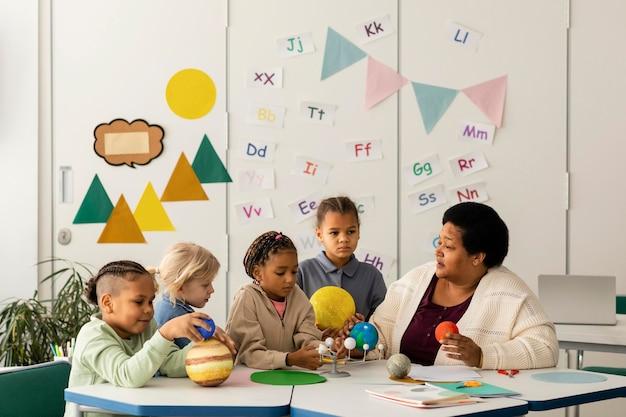 Mujer enseñando a los niños sobre los planetas