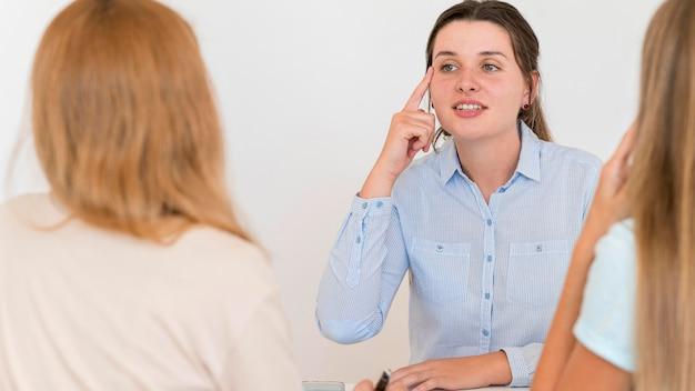 Mujer enseñando a otras personas el lenguaje de señas
