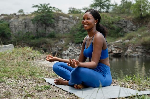 Mujer enseñando una pose de yoga al aire libre