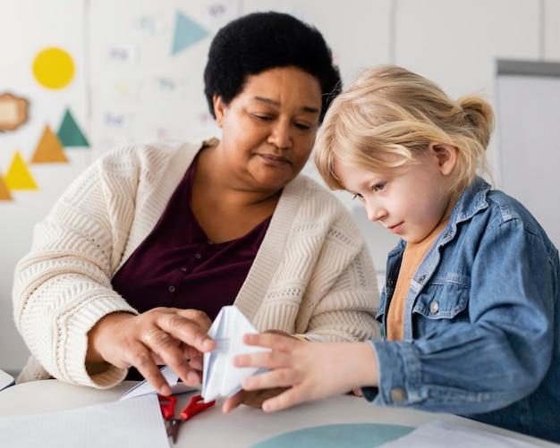 Mujer enseñando a su alumno origami