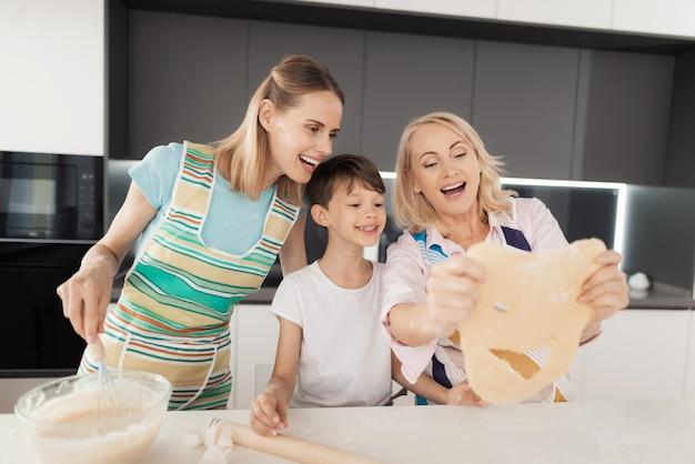 Una mujer está enseñando a su hijo a cocinar galletas caseras.