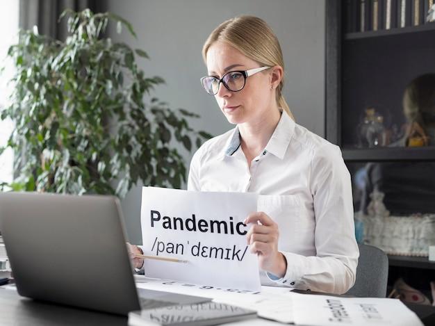 Mujer enseñando a sus alumnos la definición de pandemia en línea