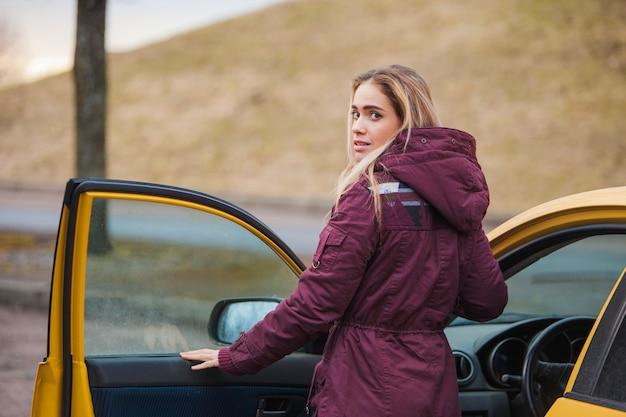 Mujer entrando en un coche amarillo