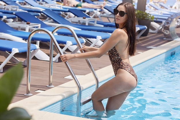 Mujer entrando en la piscina, morena mujer vistiendo bikini con estampado de leopardo y gafas de sol negras posando con salones en el fondo.