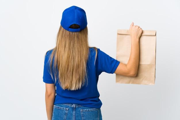 Mujer de entrega de alimentos y protección contra el coronavirus con una máscara sobre una pared blanca aislada en la posición posterior