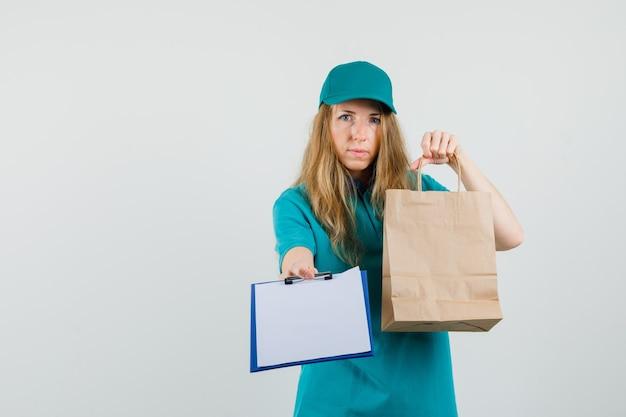Mujer de entrega con bolsa de papel y presentación de portapapeles en camiseta, gorra