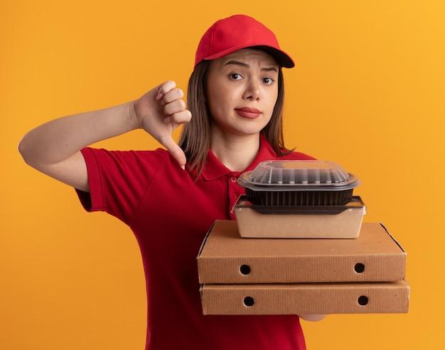 Mujer de entrega bonita seria en uniforme pulgar hacia abajo y sostiene paquetes de comida de papel en cajas de pizza