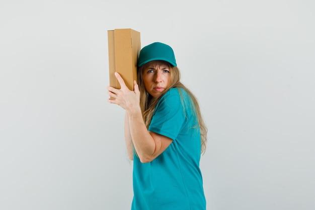 Mujer de entrega con caja de cartón cerca de su oreja en camiseta, gorra y con curiosidad.