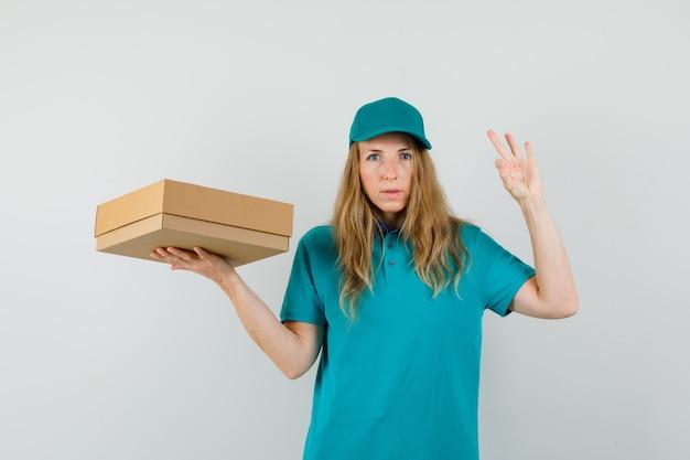 Mujer de entrega con caja de cartón con gesto ok en camiseta, gorra y mirando confiado.