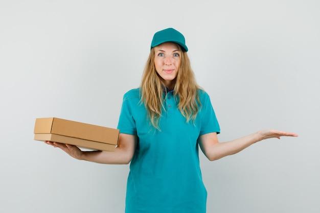 Mujer de entrega con caja de cartón con palma extendida en camiseta, gorra y mirando feliz.