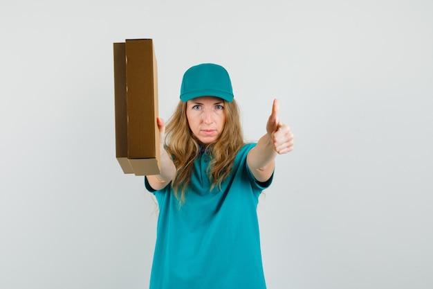 Mujer de entrega con caja de cartón con el pulgar hacia arriba en camiseta, gorra