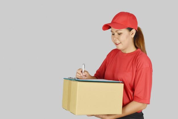 Mujer de entrega con caja de paquetería y escribir la lista de clientes en el portapapeles.