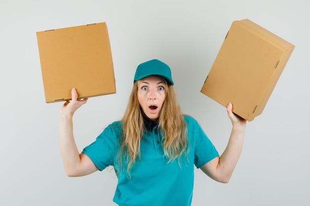 Mujer de entrega con cajas de cartón en camiseta, gorra y mirando sorprendida.